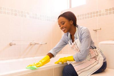 Woman cleaning bathtub.