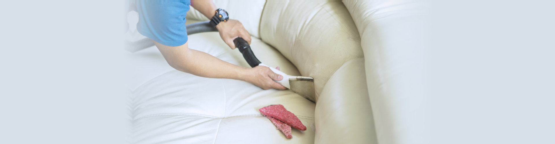 Housekeeper cleans couch with a vacuum cleaner.
