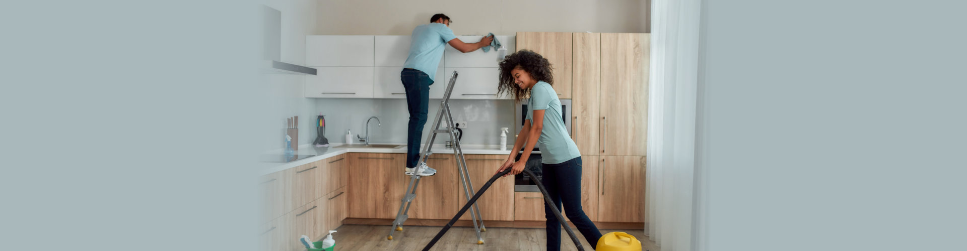 Cleaning experts. Two young professional cleaners in uniform working together in the kitchen. Young caucasian man.