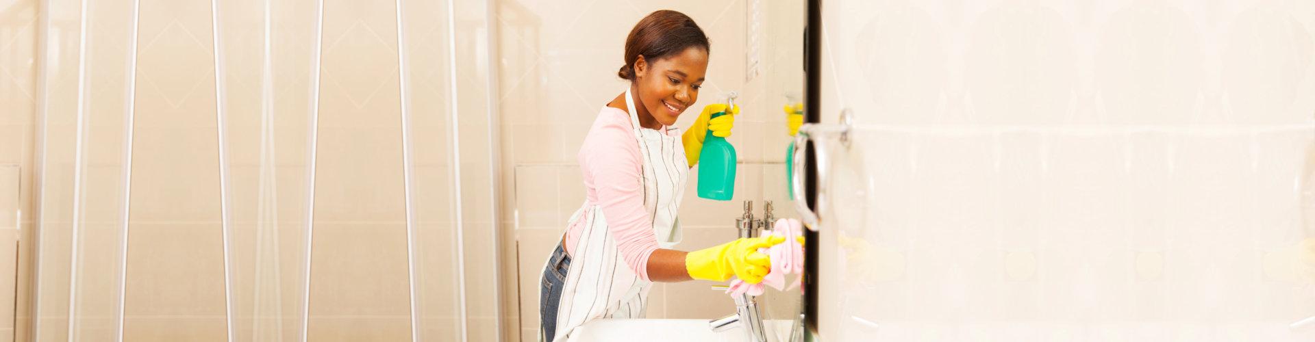 Woman cleaning bathroom mirror.